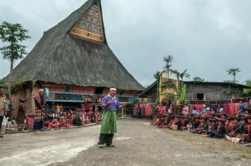Master-of-ceremonies-in-front-of-traditional-Karo-Batak-longhouse,-Lingga-Brastagi,-North-Sumatra