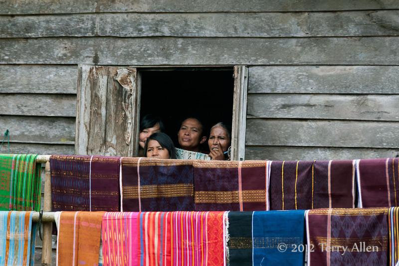 Peeking-out-the-window-at-the-dancers,-Lingga-Brastagi,-North-Sumatra