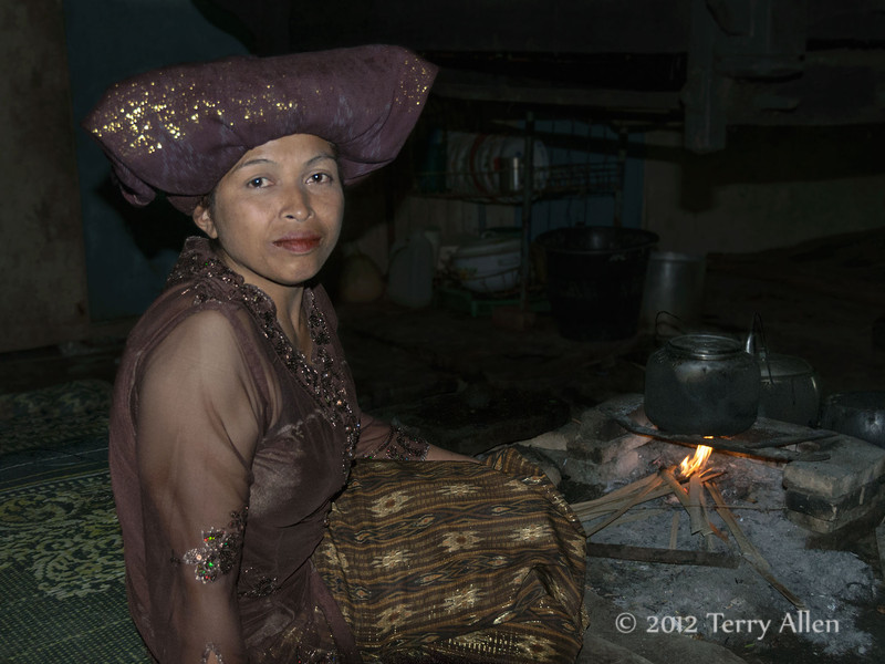 Batak-woman-sitting-by-cooking-fire-in-traditional-longhouse,-Lingga-Brastagi,-North-Sumatra<br /> <br /> The Karo Batak longhouses are large buildings without partitions that accommodate 4 families, each with their own cooking fire.  They are completely dark inside and challenging for photography without flash (and the shadows you get).  Critiques welcome.