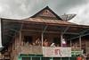 Typical wooden house with spectators on balcony, near Liwa, West Lampung, Sumatra