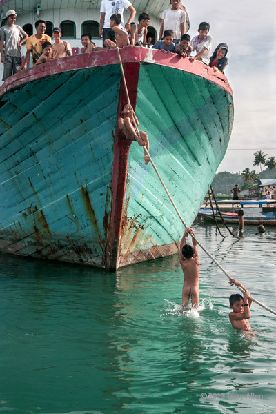 Boys showing off by climbing the anchor rope so they can dive back into the water, Teluk Dalam, Nias Island, Sumatra