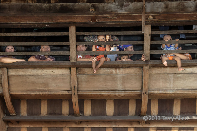 Curious villagers watching the war dances from a traditional Nias house, Bawomataluo village, Nias Island.