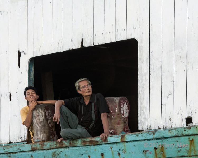 Man and boy sitting on the gunwale of an old boat, Teluk Dalam, Nias Island, Sumatra