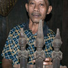 Nias villager with a carved artifact from the chief's house, Bawomatuluo- village, Nias Island, Sumatra