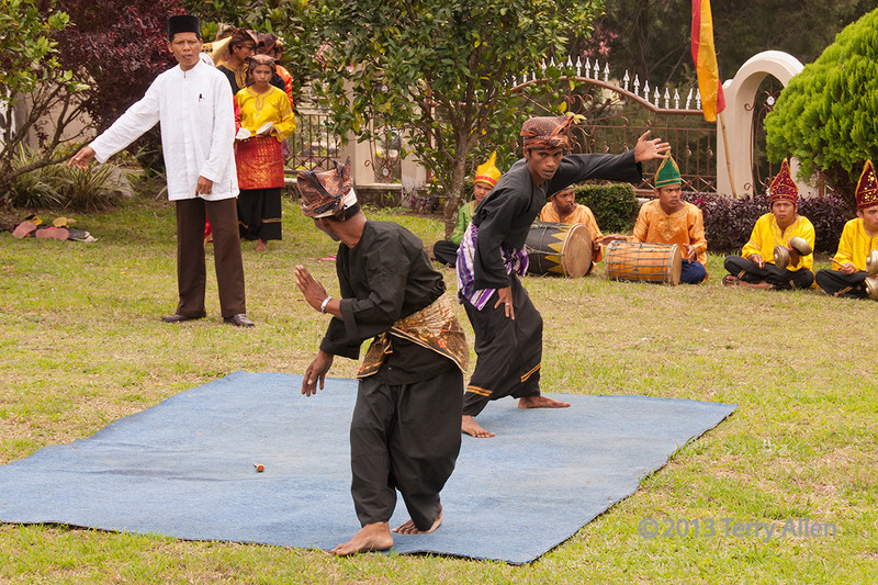 Minangkabau men demonstrating a traditional fighting match, Cupek, West Sumatra<br /> <br /> The fellow in the white coat is the judge and referee, who scores the fight and decides who wins.