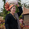 Matron in traditional dress in wedding procession carrying food for the wedding feast on her head.