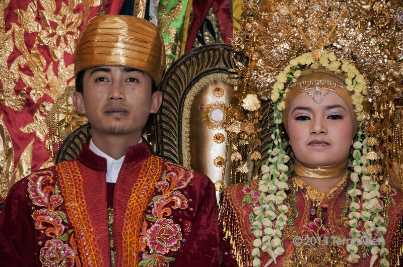 "Wedding portrait, Minangkabau wedding couple, Cupak, West Sumatra<br /> <br /> Previously I posted several galleries from the first half of our circumnavigation of Sumatra (Singapore to Nias Island).  From Nias Island we continued on to West Sumatra (Padang area), the home of the Minangkabau people, a matrilineal society that live in the highlands of West Sumatra.  Although matrilineal, the Minankabau are Islamic, but with remnants of animism, a nature-based philosophy.<br /> <br /> For a highly colourful wider angle view of the wedding party, and for a very rare photo of the photographer, see here <a href=""http://goo.gl/SBIIm"">http://goo.gl/SBIIm</a>"