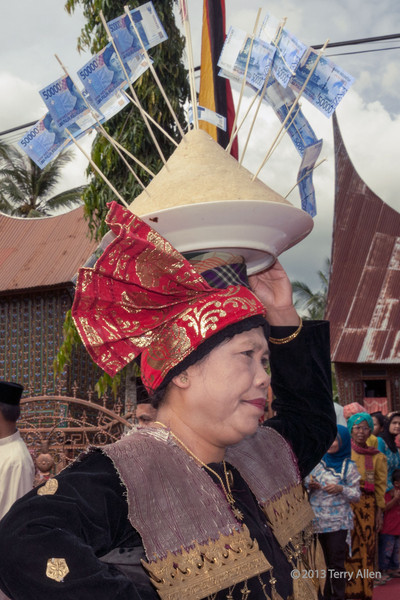 Minangkabau woman carrying platter with money to wedding feast, Solok, West Sumatra