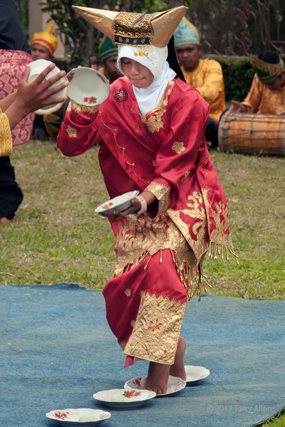 """Don't try this at home!<br /> <br /> Update: Lots of problems commenting today!  Not for lack of trying.  Sorry if I missed you!<br /> <br /> Minangkabau woman concentrating on performing the traditional egg dance, Cupek, West Sumatra<br /> <br /> This is a traditional egg dance (the band playing the music is in the background) done by the Minangkabau young women and men.  It involves balancing dishes in both hands while moving across a series of shallow bowls that contain eggs.  The trick is to not dump the eggs out of the bowls, not break the eggs, not to step outside the bowls, and not break the dishes - all while wearing traditional clothing, moving in time to the music, and looking graceful.  Not as easy as it looks, and requires excellent balance. <br /> <br /> For a couple more photos that show additional details of the egg dance, see here: <a href=""""http://goo.gl/NKsuy6"""">http://goo.gl/NKsuy6</a>"""