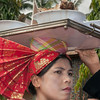Minangkabau woman carrying platter of food to wedding feast, Solok, West Sumatra