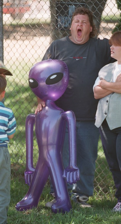 """. David Bloom of Clarkston yawns as he enjoys a circus in Holly, Mich., Sunday, July 11, 1999.  The \""""alien\"""" balloon he is holding he bought for his son."""