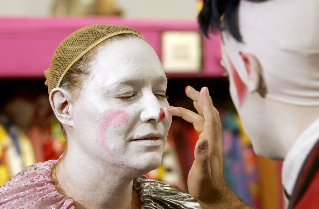 . Clown College at the Parade Company in Detroit. Clowns from Ringling Brothers held a clown college for some of this areas distinguished business people who will dress up and march in this years Thanksgiving Day Parade. Here Ringling Brothers clown Leo (right) works on Donna Walton\'s face applying pink face paint to her nose.