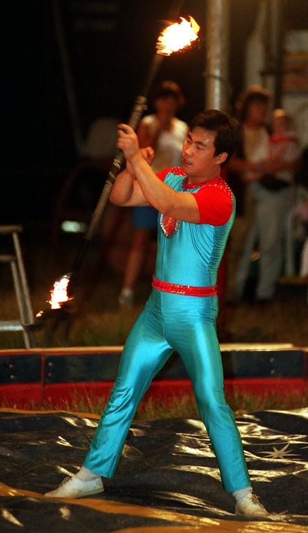 . A preformer twirls a fire baton during the Carson & Barnes circus in Highland.