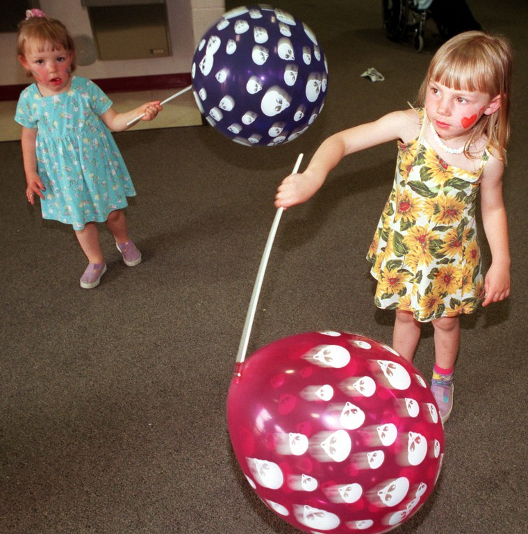 . Kari, 2,  (left) and Amanda,4, Feigley twirls their Alien Balloons at the Cole Indoor Circus last weekend at  Milford High.