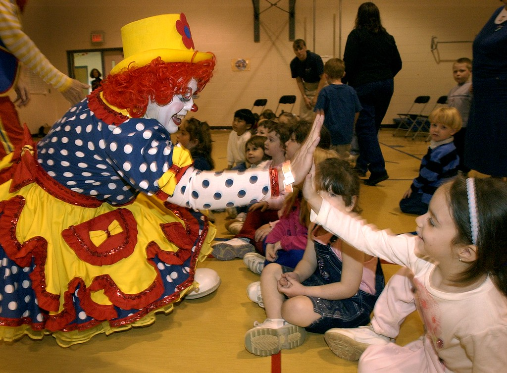 """. \""""Slo-Poke\"""" the clown gets a high-five from 4 year old Lily Sheppard at Axford Elementary School. The Royal Hanneford Circus brought in a mini circus for about 300 students. The circus has performances at The Palace of Auburn Hills this week."""