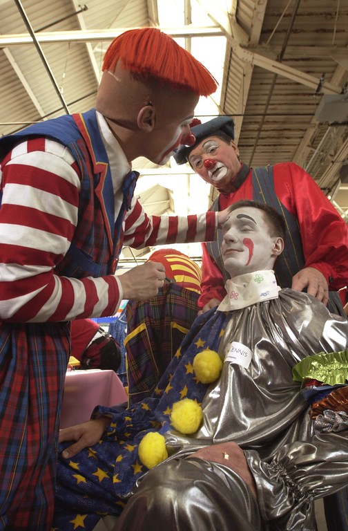 . Clown College at the Parade Company in Detroit. Clowns from Ringling Brothers held a clown college for some of this areas distinguished business people who will dress up and march in this years Thanksgiving Day Parade. Here Ringling Brothers clown Steve Copeland (left) of Walterboro, South Carolina works on the face makeup of Dennis Pietrowski (seated) of Troy, while fellow Ringling Brothers clown \'Fudi\'  of Budapest, Hungary watches (upper right)