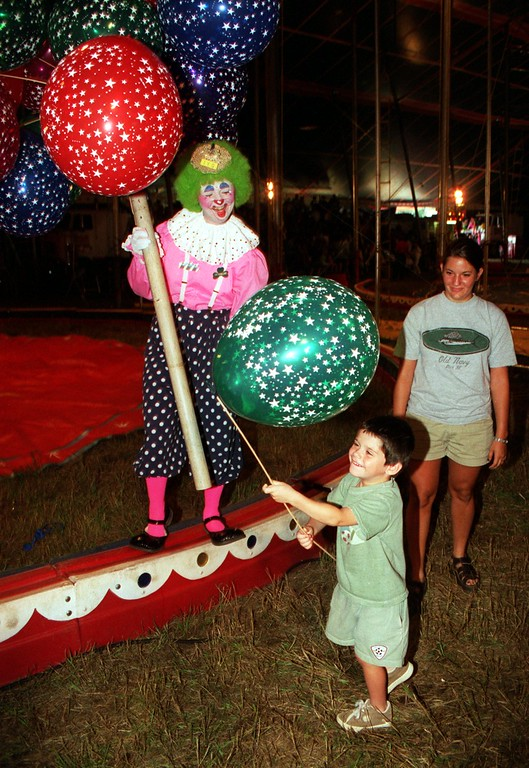 . Dillon Polycn, 4, of Milford is all smiles after getting a balloon from a clown during the Carson & Barnes circus in Highland as his babysitter Andrea Licavoli watches.