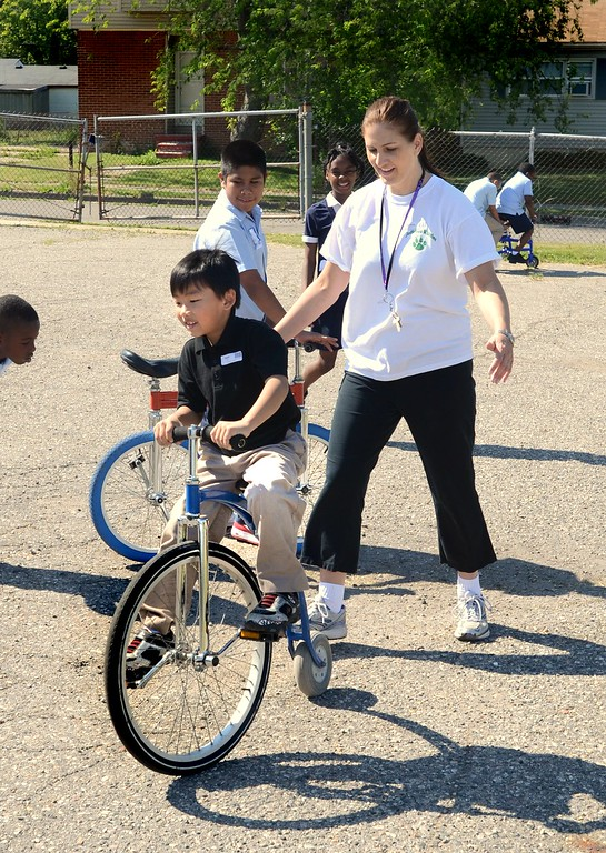 . ***WITH VIDEO***   Kevin Vang, 9, gets help riding a circus bike from teacher Ellen Dunaj at Jefferson Whittier School in Pontiac.  Kirk in the Hills of Bloomfield sponsored the unique learning experience for the students call Circus Amongus.  The second graders trained on 10 different circus acts and put on a big top show for the entire school in the afternoon.   Friday, June 8, 2012.  The Oakland Press/TIM THOMPSON