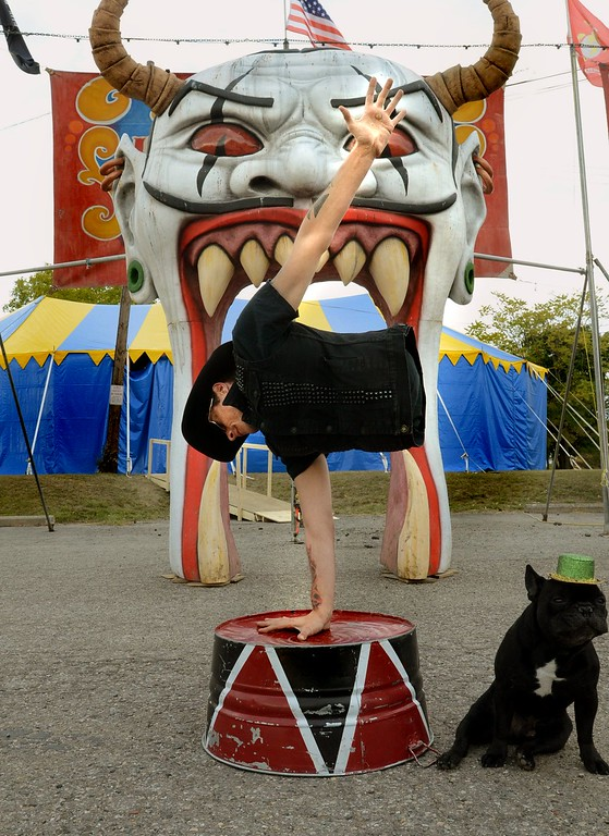 . Short E., a legless man with Mr. Buggles, does a handstand at the entrance to Hellzapoppin Circus Sideshow on Oakland Ave. in Pontiac.  Tuesday, October 20, 2015.  Tim Thompson-The Oakland Press