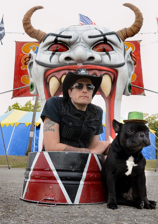 . Short E., a legless man with Mr. Buggles at the entrance to Hellzapoppin Circus Sideshow on Oakland Ave. in Pontiac.  Tuesday, October 20, 2015.  Tim Thompson-The Oakland Press