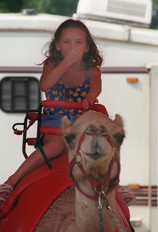 . Kayla Wagner, age 8, of Waterford, Mich., pinches her nose because she doesn\'t like the smell of the camel she is riding, prior to the start of the Kelly Miller Circus, held in Holly, Mich., Tuesday, August 7, 2001.  Wagner liked the ride, just not the smell.