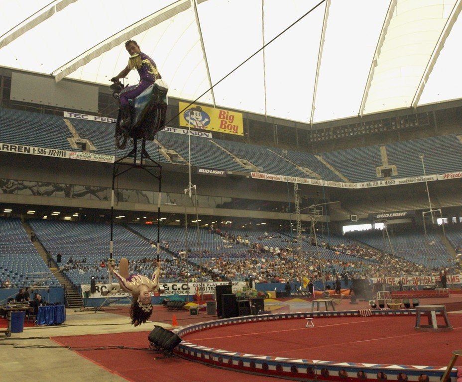 . Incline Cycle act at the Schrine Circus Xtream at the Pontiac Silverdome. The man above rides his motor cycle on a wire to the near top of the Silverdome with this lady acrobat swinging below.