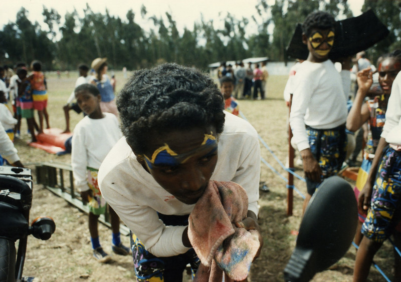 Ayanaw Tadesse removing his make-up in Marc LaChance, the Circus Ethiopia Founding Director's, motorcycle mirror