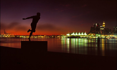 Gerome , a Canadian Runners Statue in the forgroud at Stanley Park with the Vancouver City Skyline as the backdrop