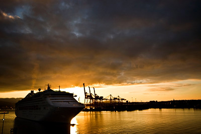 Cruise Ship coming home from Alaska. dramatic sunrise setting with Vancouvers Harbour Cranes as a backdrop setting