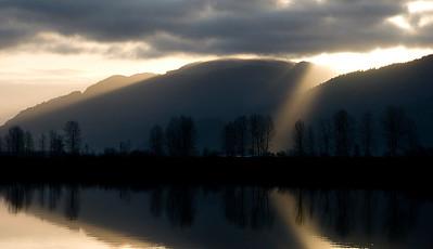 Sun peeking thru the dark clouds  by the Fraser River