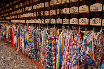 Ema and crane dedications. Kitano Tenmangu, Kyoto. (Ema are wooden plaques upon which people write their wishes. The thousand crane streams serve the same function.)