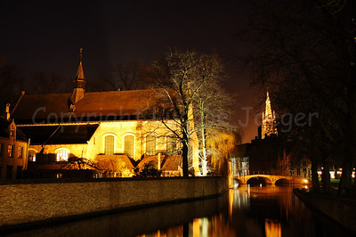 Night image of the Wijngaardplein. To the left you can see the church of the Beguinage (Begijnhof) and in the background you see the tower of the Church of Our Lady.