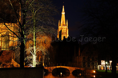 Evening shot of the bridge leading to the beguinage (Begijnhof) and, in the center, a view of the Church of Our Lady in Bruges (Brugge), Belgium. Shot around Xmas 2006.