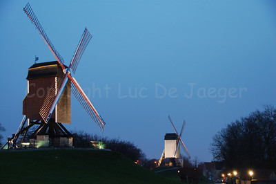 "Two of the four windmills (windmolens) along the Kruisvest in Bruges (Brugge), Belgium. To the left is the 2nd mill, counting from the Kruispoort, named ""Sint-Janshuismolen"" (built in 1770). This windmill is still working today and grinds grain. In the middle of the photo, in the background, is the 1st windmill, counting from the Kruispoort, named ""Bonne-Chièremolen"" (built in 1844). Shot at sunset."