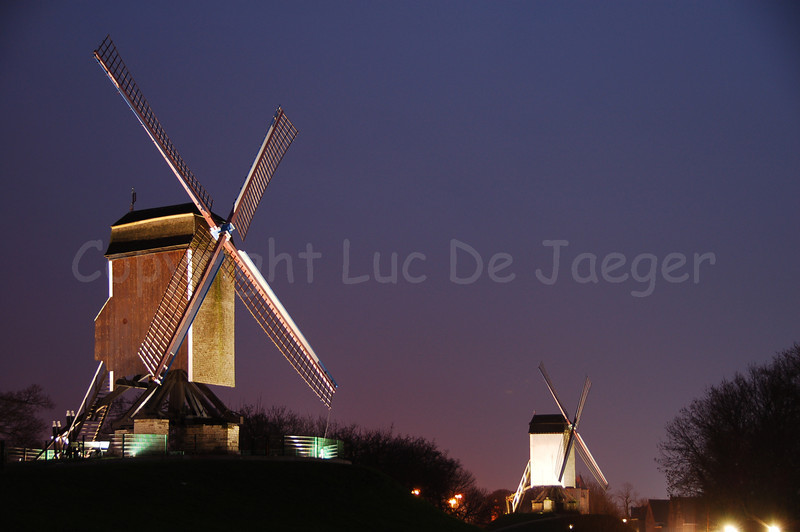 """Two of the four windmills (windmolens) along the Kruisvest in Bruges (Brugge), Belgium. To the left is the 2nd, counting from the Kruispoort, named """"Sint-Janshuismolen"""" (built in 1770). The Sint Janshuis Mill grinds grain and is still operating today. In the middle of the photo is the 1st mill, counting from the Kruispoort, named """"Bonne-Chièremolen"""" (built in 1844). Shot at sunset."""