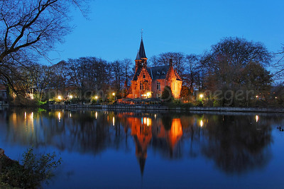 Evening image of the Minnewater Castle (Minnewaterkasteel) in the Minnewaterpark in Bruges (Brugge), Belgium.