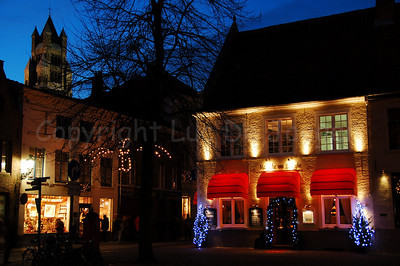 Evening shot of the restaurants at the Guido Gezelleplein near the Church of Our Lady in Bruges (Brugge), Belgium. Shot around Xmas 2006.