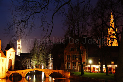 Evening shot of the Wijngaardplein in Bruges (Brugge), Belgium with the Church of Our Lady (Onze-Lieve-Vrouwekerk) to the right and the Saint Saviour's Cathedral (St Salvatorskathedraal) in the background to the left. In front of you is the bridge leading to the Beguinage (Begijnhof).
