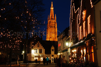 Evening shot of the Walplein with view on the Church of Our Lady in Bruges (Brugge), Belgium. The trees and buildings in the square were decorated with nice Xmas lighting.