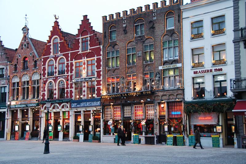 Pubs and restaurants on the Market Square in Bruges (Brugge), Belgium. Shot at sunset.