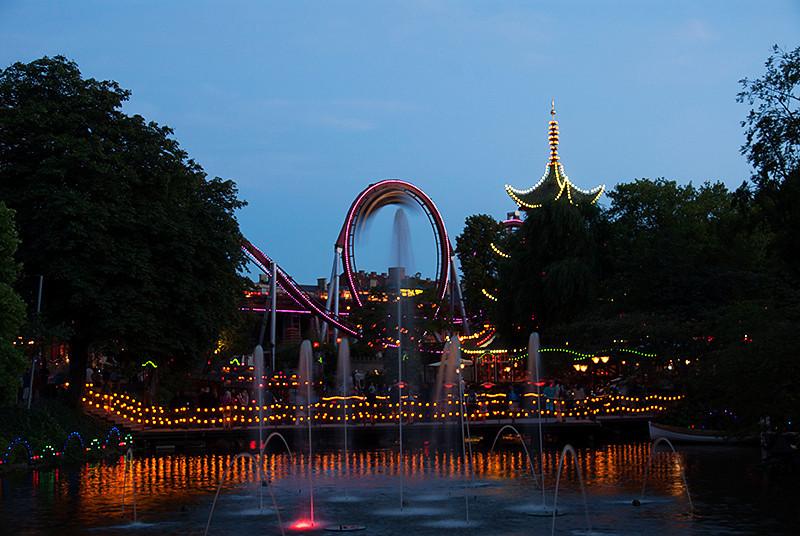 Dæmonen (The Demon) roller coaster in the middle, in the Danish amusement park, Tivoli Gardens, Copenhagen, Denmark at dusk