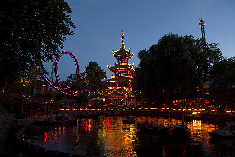 Dæmonen (The Demon) roller coaster on the left, in the Danish amusement park, Tivoli Gardens, Copenhagen, Denmark at dusk