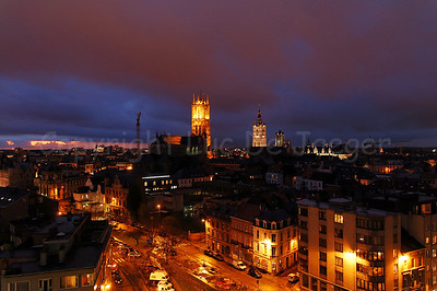 The skyline of the city of Ghent (Gent), Belgium with the three Towers. On the left is the Cathedral of St Bavo (Sint Baafskathedraal), in the center is the Belfry (Belfort) and the 3rd tower is the Church of St Nicolas (Sint Niklaaskerk). Photo captured at dusk.