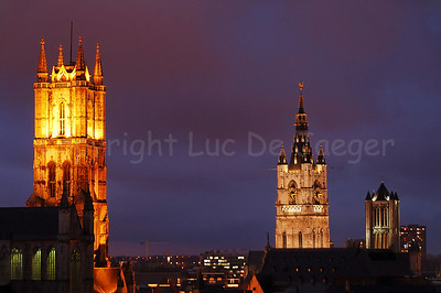 The three towers that mark the city of Ghent (Gent), Belgium. On the left is the Cathedral of St Bavo (Sint Baafskathedraal), in the center is the Belfry (Belfort) and the 3rd tower is the Church of St Nicolas (Sint Niklaaskerk). Photo captured at dusk.