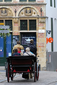 Horse and carriage lead the tourists through the medieval streets of Ghent (Gent) in Belgium.