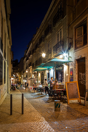 People and restaurants in the Bairro Alto district in Lisbon at dusk