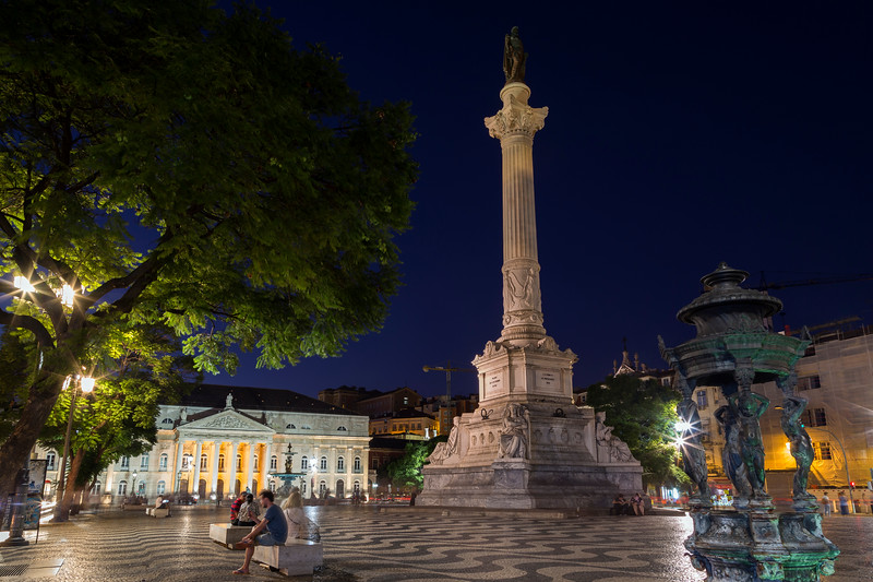 People and statue at the Rossio Square in Lisbon at night