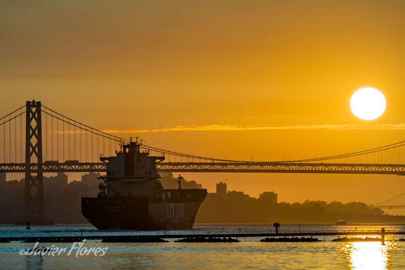 Sunset Over the Bay Bridge with Ship Heading to open sea.