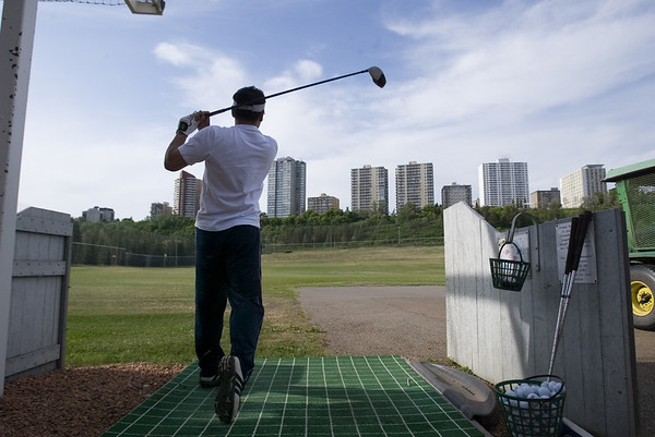 With downtown Edmonton rising in the distance and golfer practices his swing at Victoria driving range in the river valley . The city of Edmonton covers 684 square kilometers boasting one of the lowest population densities among North American cites. JCI Photo - Jeffrey S. otto