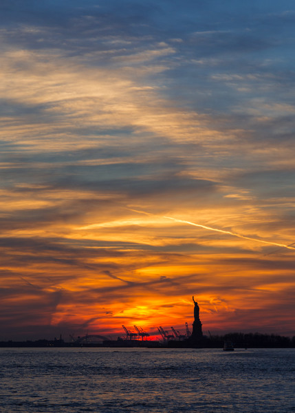 Sun setting behind the Statue of Liberty in New York.